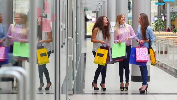 Three beautiful girls with shopping bags watch purchase on shopping center. Slow motion.