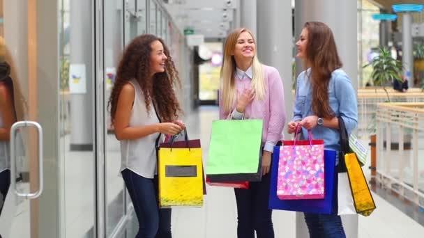 Tři nádherné dívky s nákupními zavazadly sledují nákup v nákupním středisku. Zpomaleně.