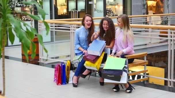 Három gyönyörű lányok bevásárló táskák néz vásárlás a bevásárlóközpontban. Lassított mozgás.