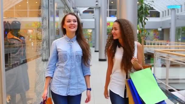 Két gyönyörű lányok bevásárló táskák megy a bevásárlóközpontban. Lassított mozgás.