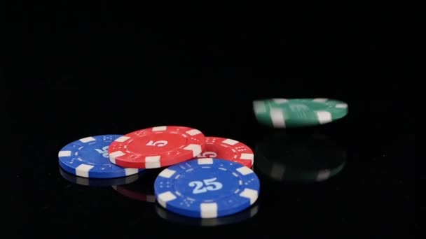 many poker chips falling on a black background. Slow motion