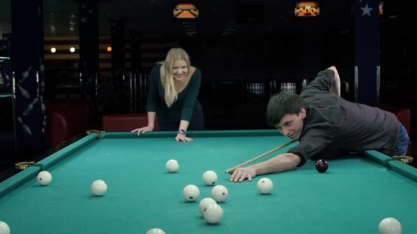 Young couple playing pool in a bar. Slow motion