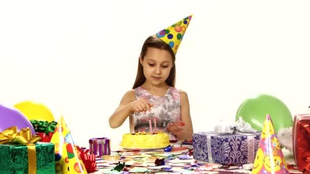Gyönyörű lány díszíti a torta gyertyákkal. A táblázatban vannak rendezve ajándékok