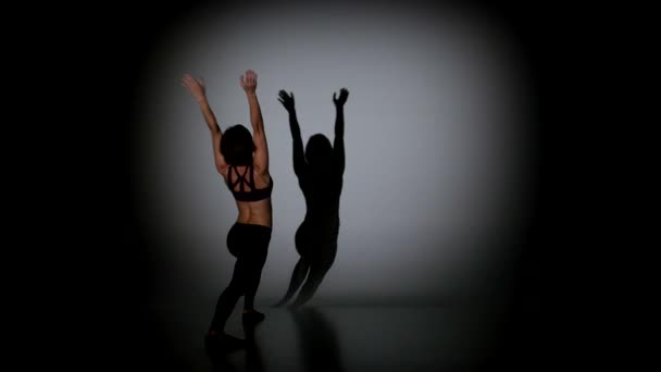 Young girl dancing acrobatic contemporary on black background, spot light