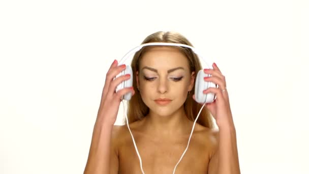 Sexy žena v bílé košili poslouchá a tančí na hudbu používající sluchátka
