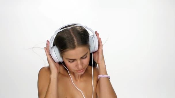 schöne Frau mit Kopfhörern, die der Musik lauscht, mit flatternden Haaren auf weißem Hintergrund. Zeitlupe.
