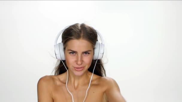 Krásná samice ve sluchátkách naslouchá hudbě a třepetala se ve větru na bílém pozadí. Zpomaleně.