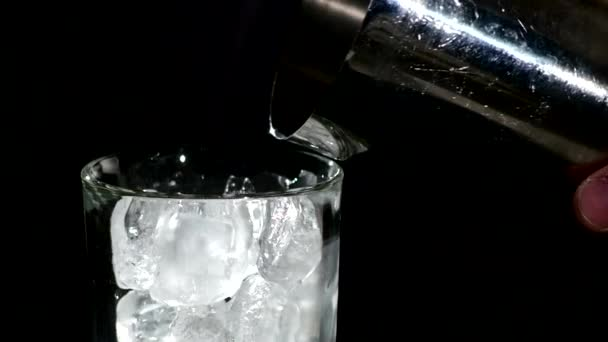 Cola glass with falling ice cubes over black