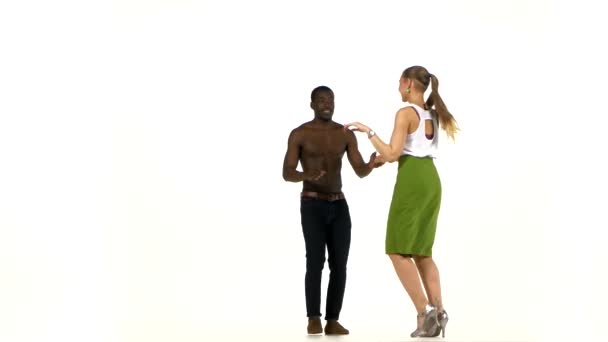 Social latino dancers girl with ponytail and afro american man with naked torso go on dancing on white
