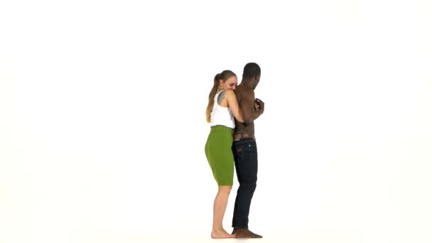 Girl and afro american man with naked torso barefoot dancing social latino dancing on white