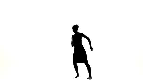 Beautiful dancer woman starts dancing social latino dance barefoot, on white, silhouette