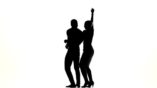 Couple of social latino dancers girl with ponytail and afro american man with naked torso go on dancing on white, slow motion, silhouette