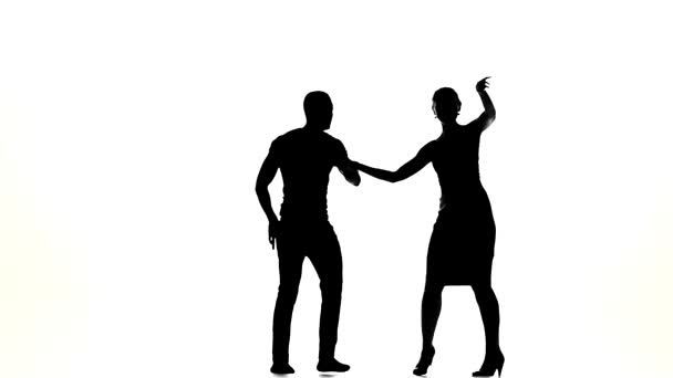Talanted couple of social latin dancers continue dancing on white, slow motion, silhouette