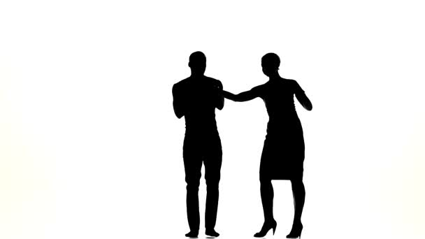 Attractive social latino dancers, european girl and afro american man go on dancing on white, silhouette, slow motion