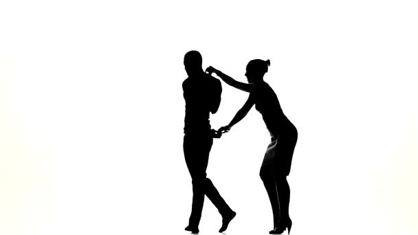 Couple of social latino dancers, european girl and afro american man go on dancing on white, slow motion, silhouette