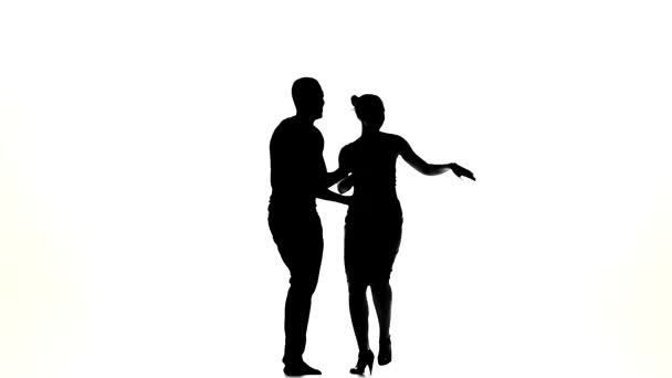Couple of social latino dancers go on dancing on white, slow motion, silhouette