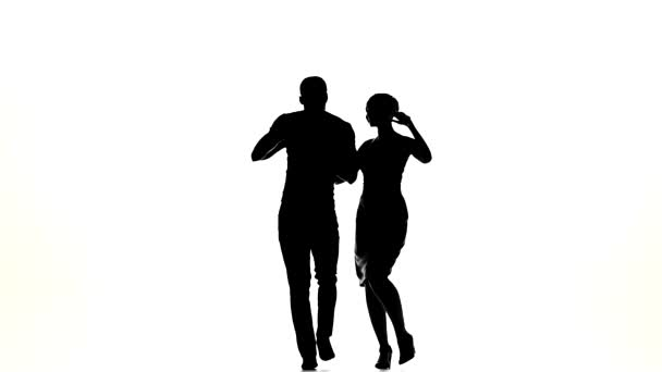 Couple of social latino dancers starts dancing on white, slow motion, silhouette