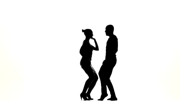 Attractive couple of social latino dancers continue dancing on white, slow motion, silhouette