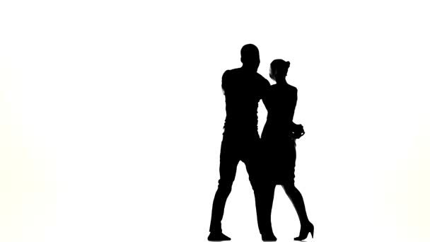 Attractive couple of social latina dancers continue dancing on white, slow motion, silhouette