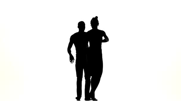 Professional couple of social latin dancers starts dancing on white, slow motion, silhouette