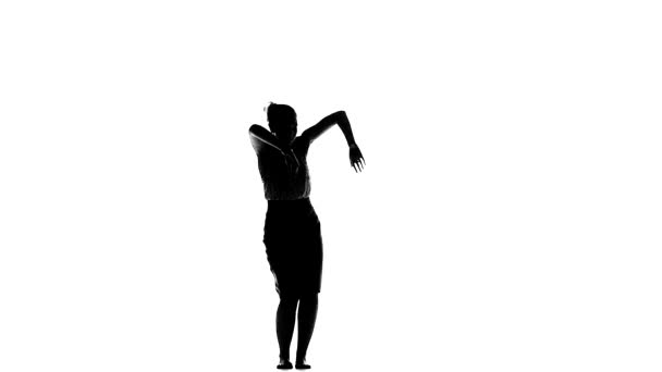 Attractive young lady dancing social latin dance, slow motion, silhouette