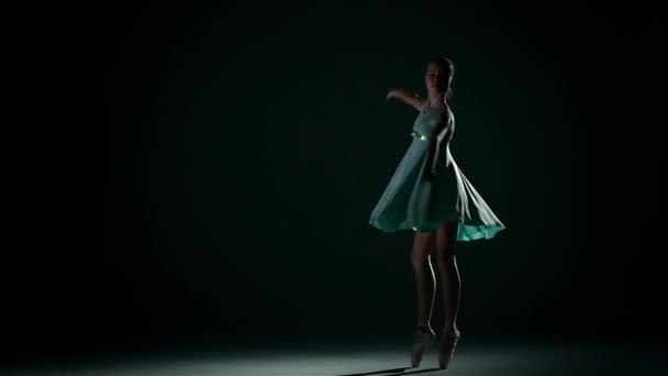 girl dances in a pretty blue dress on a dark background