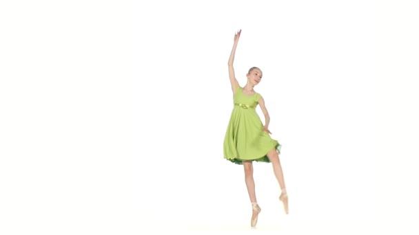 Ballerina im grünen Kleid posiert auf einem weißen. Zeitlupe