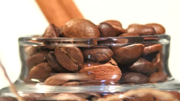 Top of little bottle with brown coffee beans and cinnamon close up