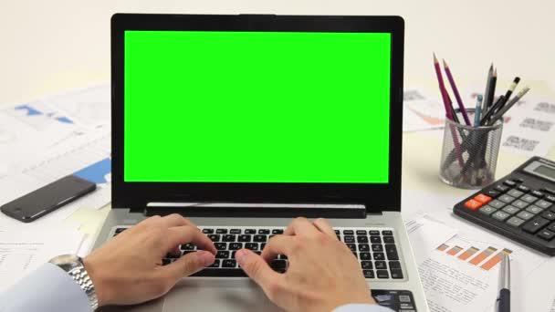 Muž rukou na klávesnici notebooku s zelenou obrazovku monitoru