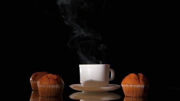 Bílý šálek horké kouření s muffiny na tmavém pozadí