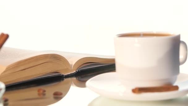 Šálek kávy s obrací stránky knihy na bílém pozadí