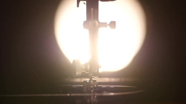 Part of antique working silver sewing machine, back light, slow motion, close up
