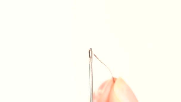 Lichtfaden durch ein Nadelloch auf weißem Hintergrund, Nahaufnahme