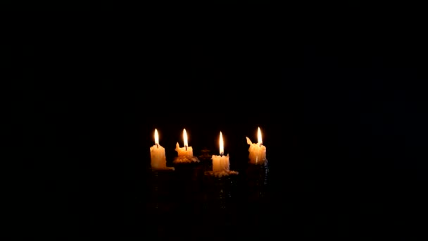 Young witch blows out the candles on a black background