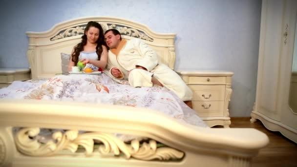 Šťastný mladý pár jíst snídani v posteli. Nabídka ráno