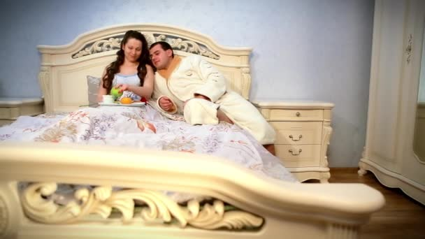 Happy young couple eat breakfast in bed. Tender morning