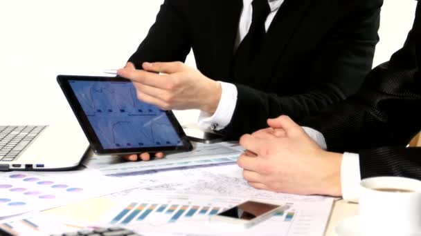 One businessman showing another, developing a business project and analyzing market data information, graphics tablet.
