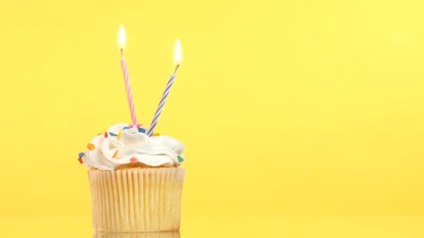 finom születésnapi cupcake két gyertya, sárga háttér