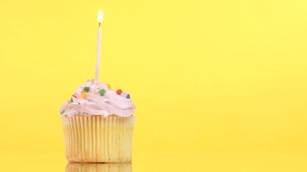 Bigné di compleanno gustoso con una candela, su sfondo giallo