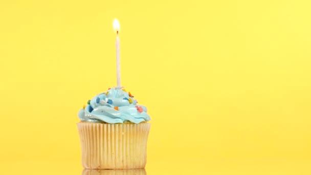 leckerer Geburtstagskuchen mit einer Kerze, auf gelbem Hintergrund.