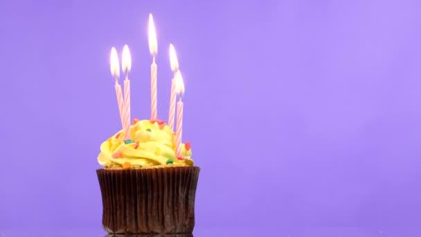 Bigné di compleanno gustoso con cinque candela, su sfondo viola