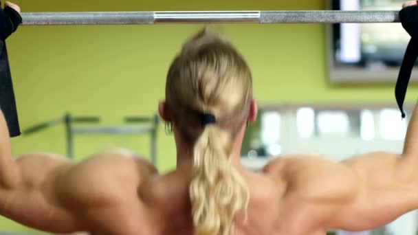 Strong man doing pull-ups on a bar in gym.