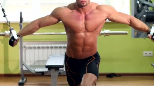 Sportovní, pohledný muž vyjde na zařízení v tělocvičně