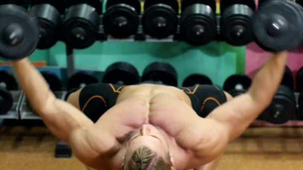 Sportsman doing exercises with dumbbell in the gym