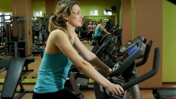 Atraktivní, sportovní dívka je jízda na kole, v posilovně fitness