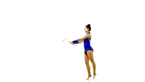 Zarte Turnerinnen tanzen mit Jonglierklubs