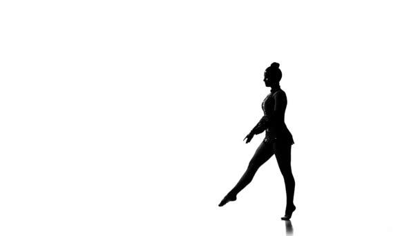 Sziluettek gyönyörű fiatal acrobat hajt végre gimnasztikai stunt. lassú mozgás