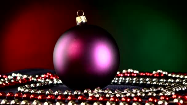 Matte purple toy for Christmas or New Year and beads, rotation, on red and green