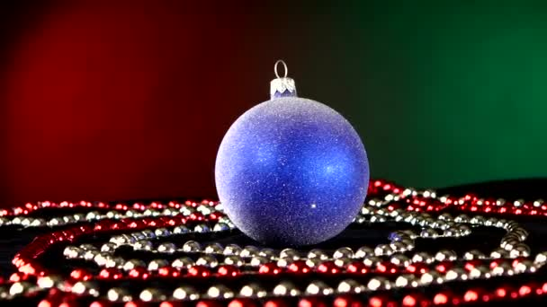 Shiny blue toy for Christmas or New Year and beads, rotation, on red and green