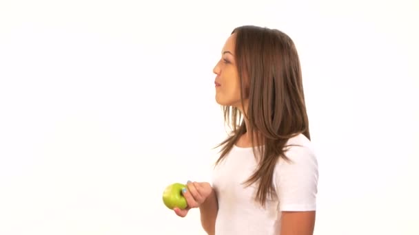 Beautiful healthy girl biting a juicy green apple, on white
